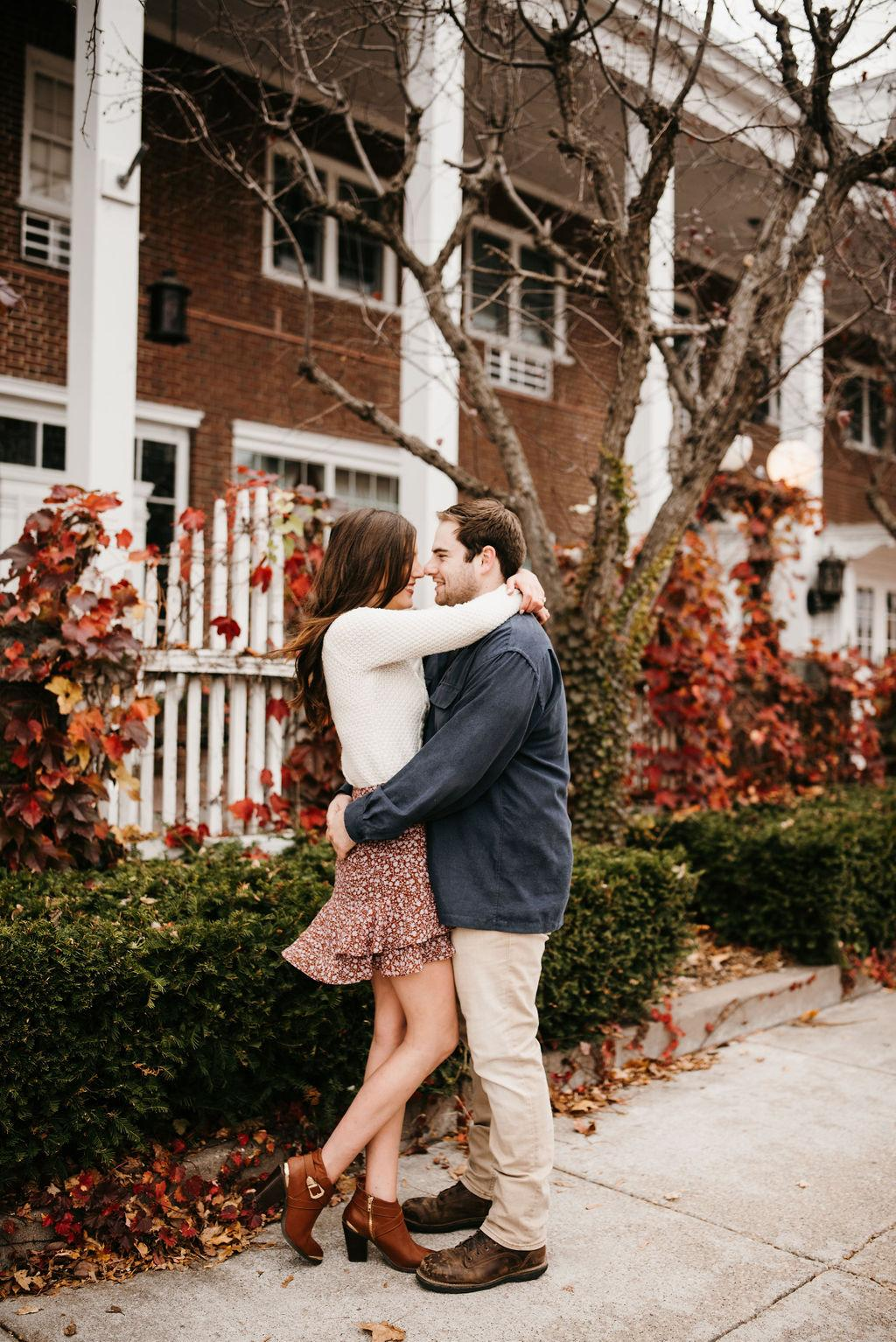 Engagement pictures of Garrett and Morgan in front of a brick building. They are touching noses and hugging.