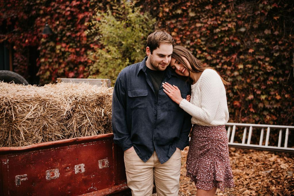 Engagement pictures of Garrett and Morgan standing in front of an ivy wall and an old truck. Morgan is leaning her head on Garrett's shoulder.