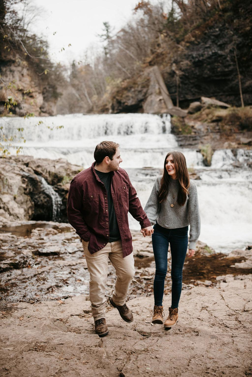 Morgan and Garrett are holding hands and walking in front of a waterfall and cliffs.