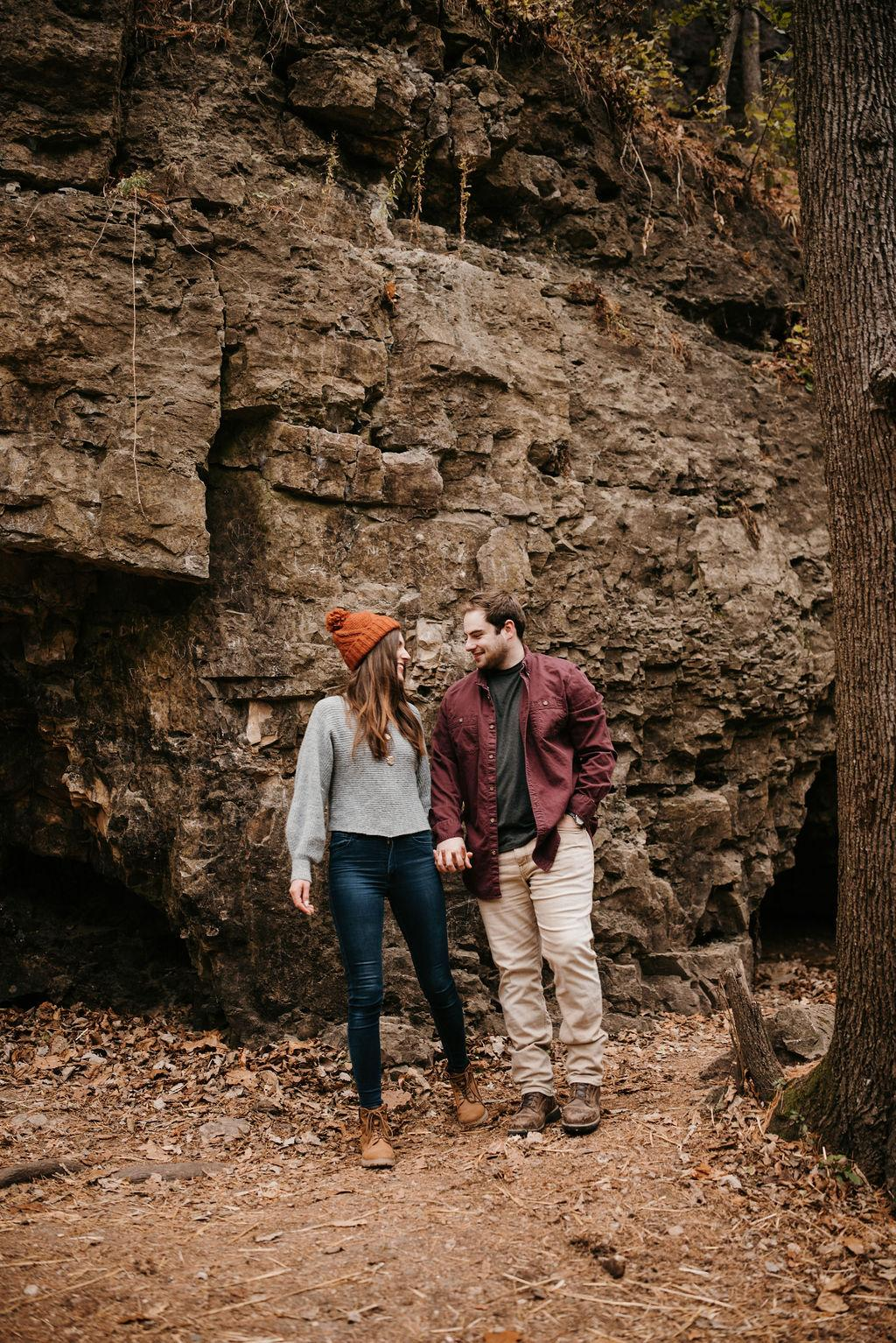 Morgan and Garrett are holding hands and smiling at each other in front of a cliff. Morgan is wearing an orange beanie.