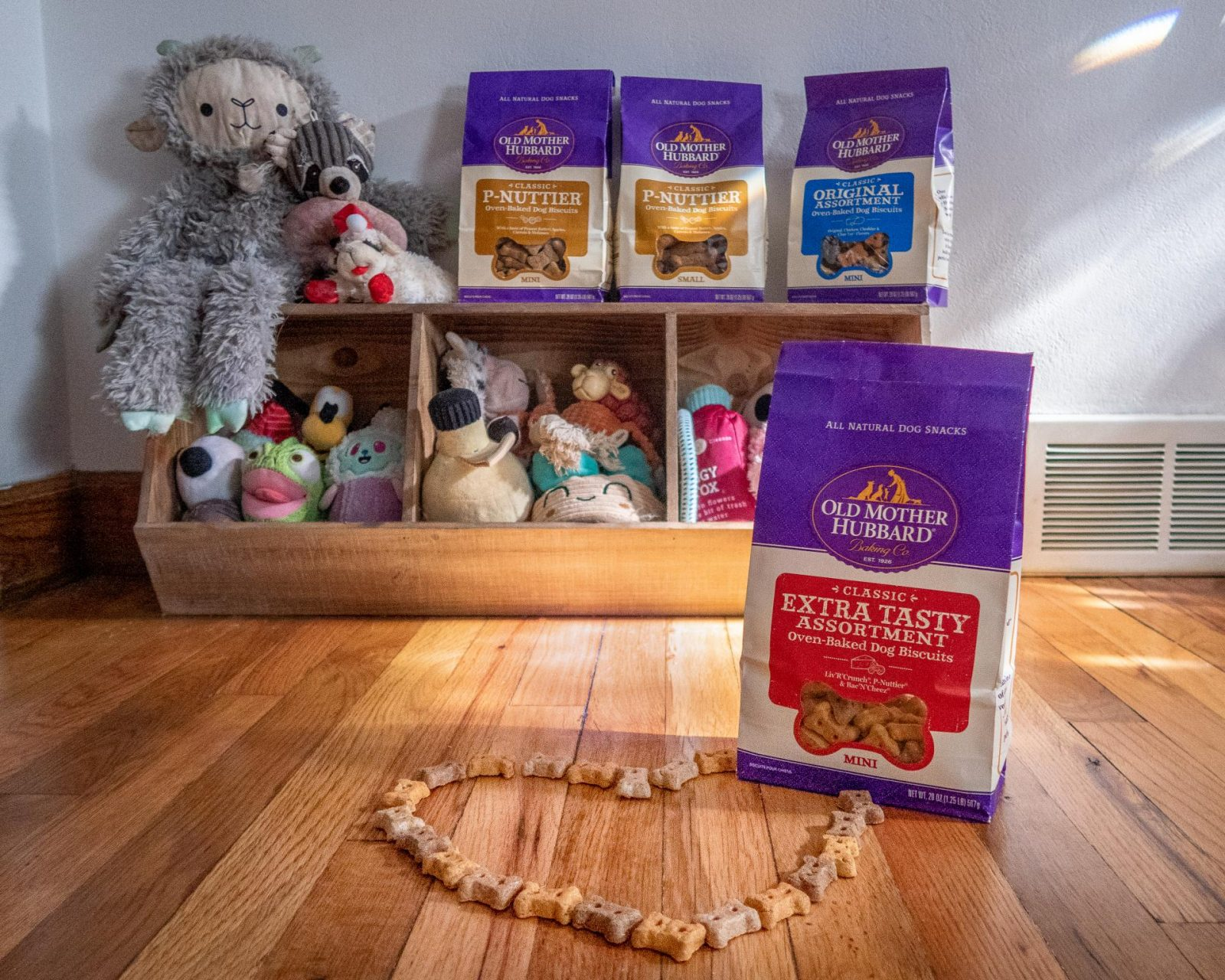 Old Mother Hubbard dog treats are lined up on Maisie the Saint Bernard's toy box, with the Extra Tasty Assortment bag in focus in front of the photos.