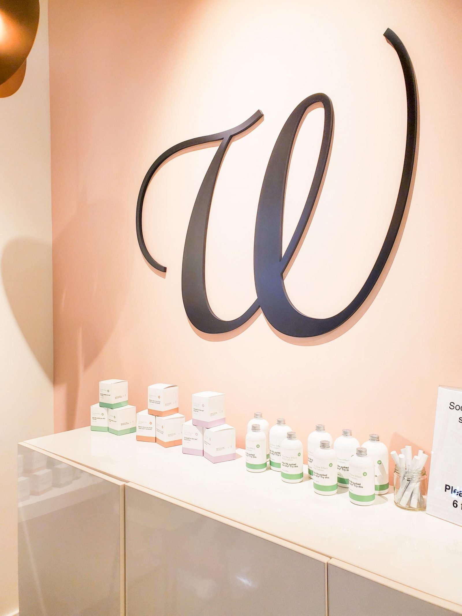 The W Nail Bar logo on a pink wall above an array of their lotions and other products