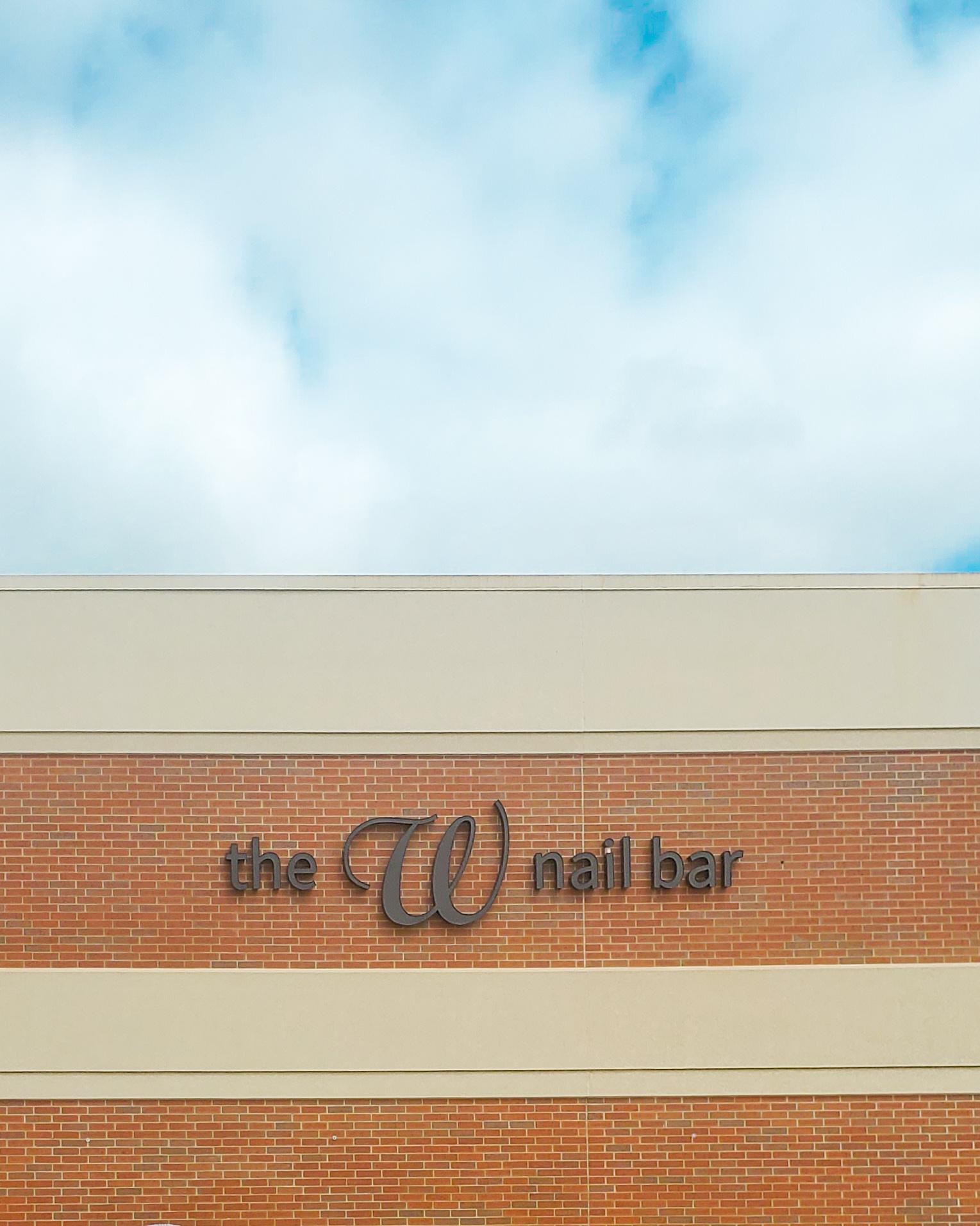The W Nail Bar sign on the outside of the Quad Cities Hy-Vee in Bettendorf, Iowa. Above the sign are blue skies with a scattering of clouds.